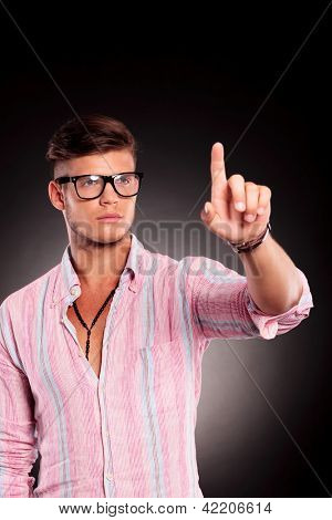young casual man pushing a button over black background
