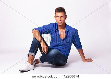 voller Länge Bild von einem schweren jungen lässig mann sitzen auf dem Boden und ein Blick in die Kamera,