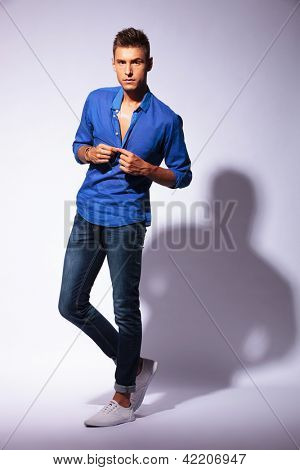 full length picture of an attractive young man unbuttoning his shirt and looking at the camera, on light background with hard shadow