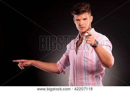 picture of a handsome young man pointing to the camera and to his side, looking at the camera, on black background