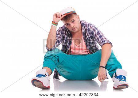 Bild von einer jungen Tänzer auf dem Boden sitzend und gedrückter, dass seinen Hut in die Kamera schaut,
