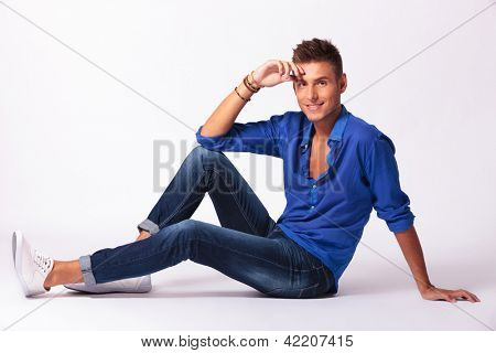 cool fashion young male model sitting on grey background and looking at the camera with a smile on his face