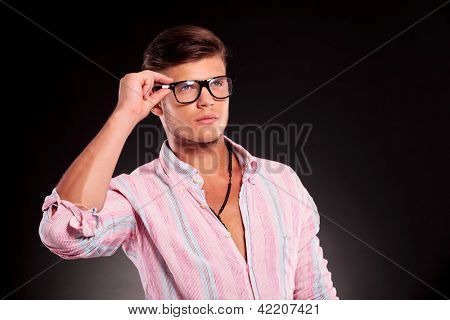 closeup picture of a gorgeous young casual man holding his eyeglasses and looking away from the camera, on a black background