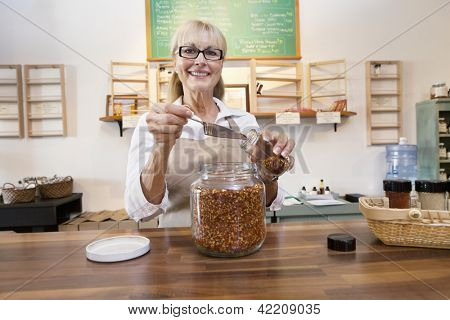 Portrait of a happy female employee pouring spice with scoop in jar