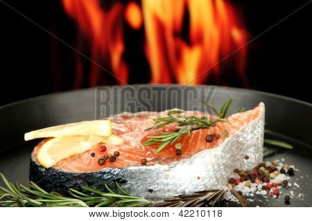 Fresh salmon steak on pan, on fire background, close up
