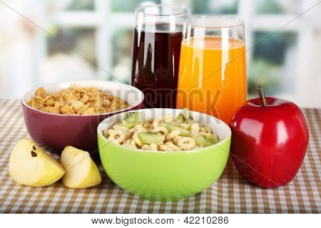 Delicious and healthy cereal in bowls with juice and fruit on table in room