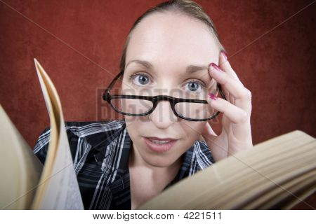 Peprlexed Woman With Big Eyes Reading A Book