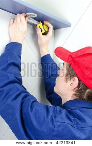 Young Tradesman In Uniform Measuring Solid-state Lighting