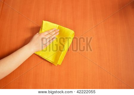 a woman cleaning furniture with yellow cloth