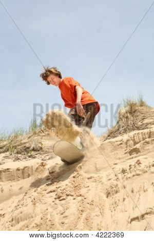 Teenager Sandboarding Down A Dune
