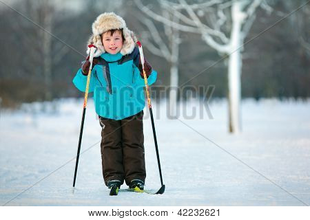 Cute five years old boy skiing on cross