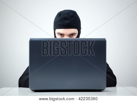 Hacker stealing information from a computer at the desk