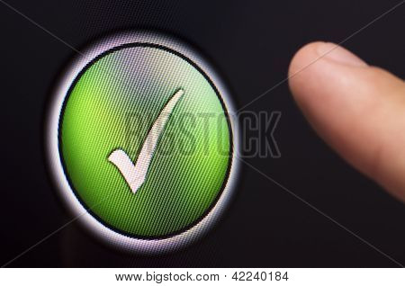 Finger Pressing A Green Tick Button On Touchscreen