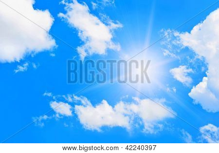 Bright sun in blue sky with clouds