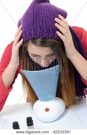 eine junge Frau mit Erkältungen und Grippe inhaliert ätherische Öle