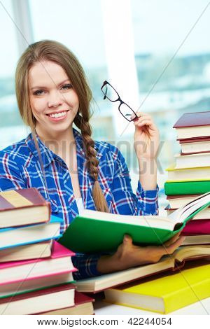 Portrait of diligent student looking at camera with open book in hands