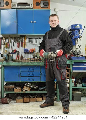 Locksmith holding angular grinder while posing in his workshop