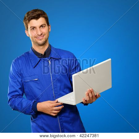 Happy Engineer Holding Laptop  On Blue Background