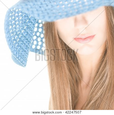 Young woman with half hidden face under blue hat.