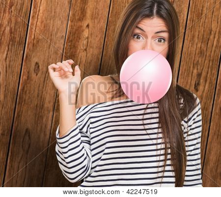 Young Woman Blowing Bubblegum against a wooden background