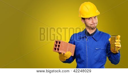 Engineer Holding Brick And Goldbar On Coloured Background