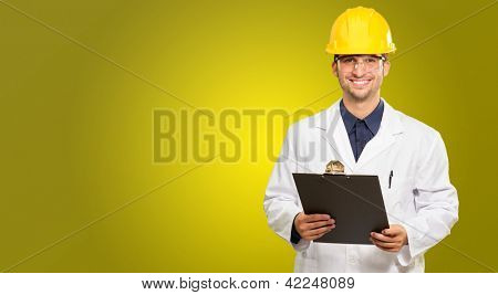 Happy Male Architect Holding Clipboard On Coloured Background