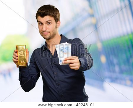 Young Man Holding Gold Bar And Euro Currency, Outdoors