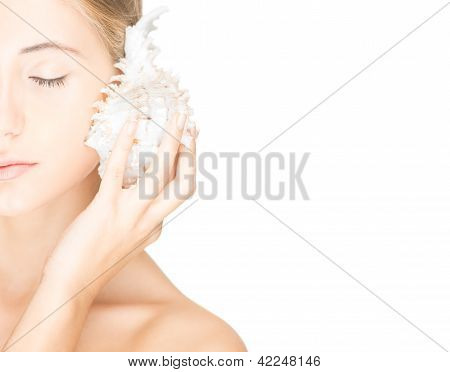 Pretty woman with seashell isolated on white.