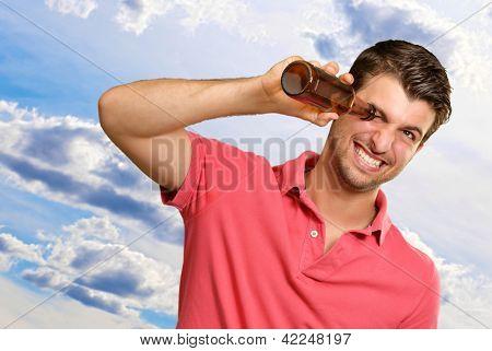 Hombre mirando dentro de una botella vacía, al aire libre