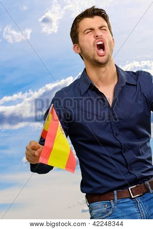 Man cheering and holding flag, outdoor