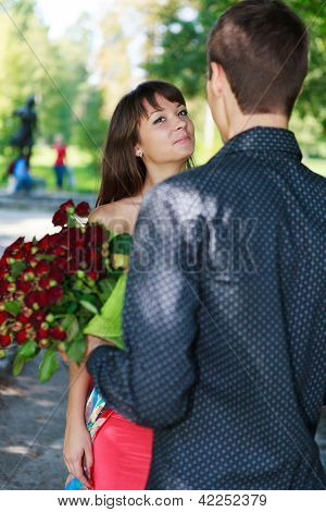 Young Man Gift A Woman A Bouquet Of Red Roses In A Summer Park