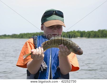 Boy trying to hold a fish