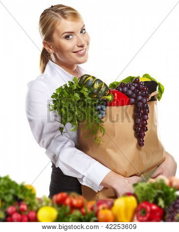 Portrait of happy business woman holding a shopping bag full of groceries on white background
