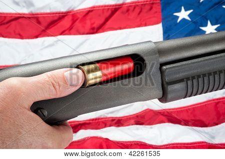 A man loads a shotgun shell into a pump action shotgun.  Shot against an American flag.
