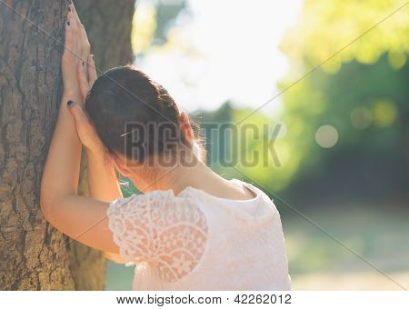 Girl Looking Out From Tree. Rear View