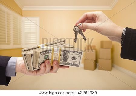 man and Woman Handing Over Cash For House Keys Inside Empty Room with Boxes.