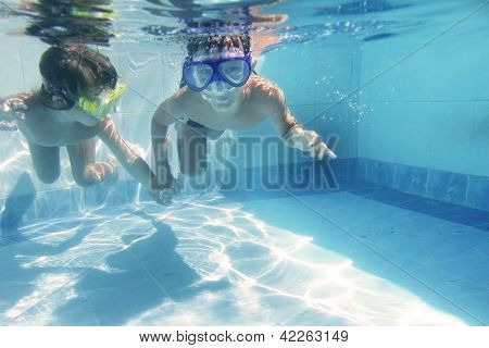 two children diving underwater in goggles