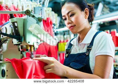 Seamstress or Chinese worker in a factory sewing with a industrial sewing machine, she is very accurate