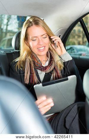 Junge geschäftsfrau, die Fahrt im Taxi, sie mit tablet-Computer und ist auf dem Handy