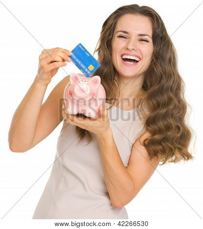 Happy Young Woman Putting Credit Card Into Piggy Bank