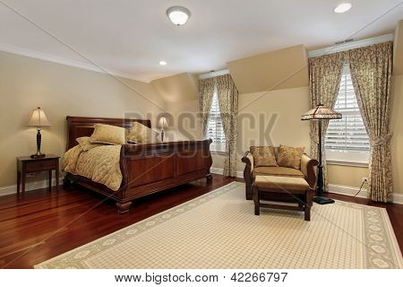 Master bedroom in luxury home with cherry wood flooring