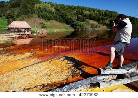 Photoreporter documenting the water pollution of a copper mine exploitation