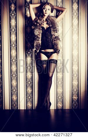 Full length portrait of a sexual fashionable woman over vintage background.