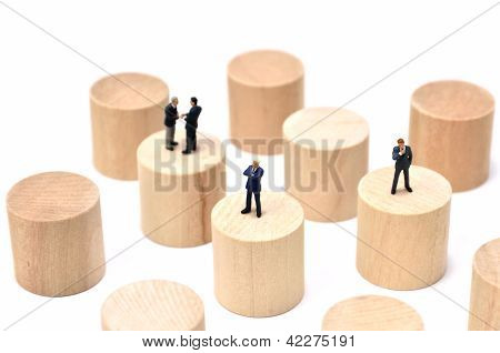 Arranged Wood Cylinder And Businessman On White Background.