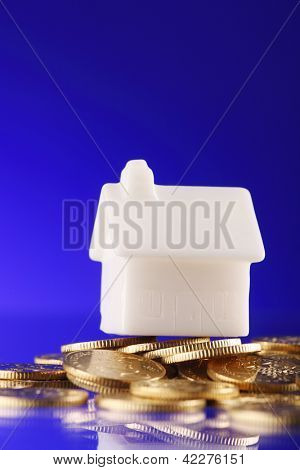 Close-up of a model home on a pile of coins