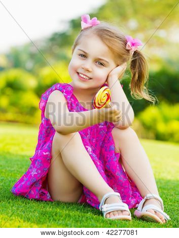 Photo of cute little girl sitting on green grass on backyard and holding in hand colorful lollipop, small child wearing pink dress outdoors in spring and eating sweet sugar candy, happy childhood