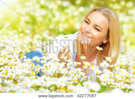 Image of sweet girl lying down on daisy glade and enjoying warm sun light, beautiful woman holding in hand little camomile flower, recreation on floral field, relaxation in rural place, spring holiday