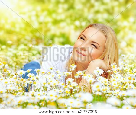 Photo of cute blond female laying down on chamomile field and looking up in sky, sunny day, warm weather, spring holiday and vacation, pretty woman enjoying beautiful nature, daisy field