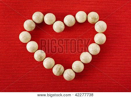 Heart shape symbol made of wooden ball on red cloth texture background