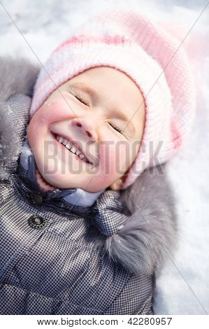Little girl is laying on a snow and smiling with closed eyes